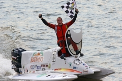 Formula One. winner Chris Fairchild expresses his jubilation to the fans while waving the checkered flag